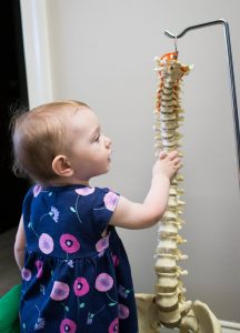 baby girl touching skeleton spine