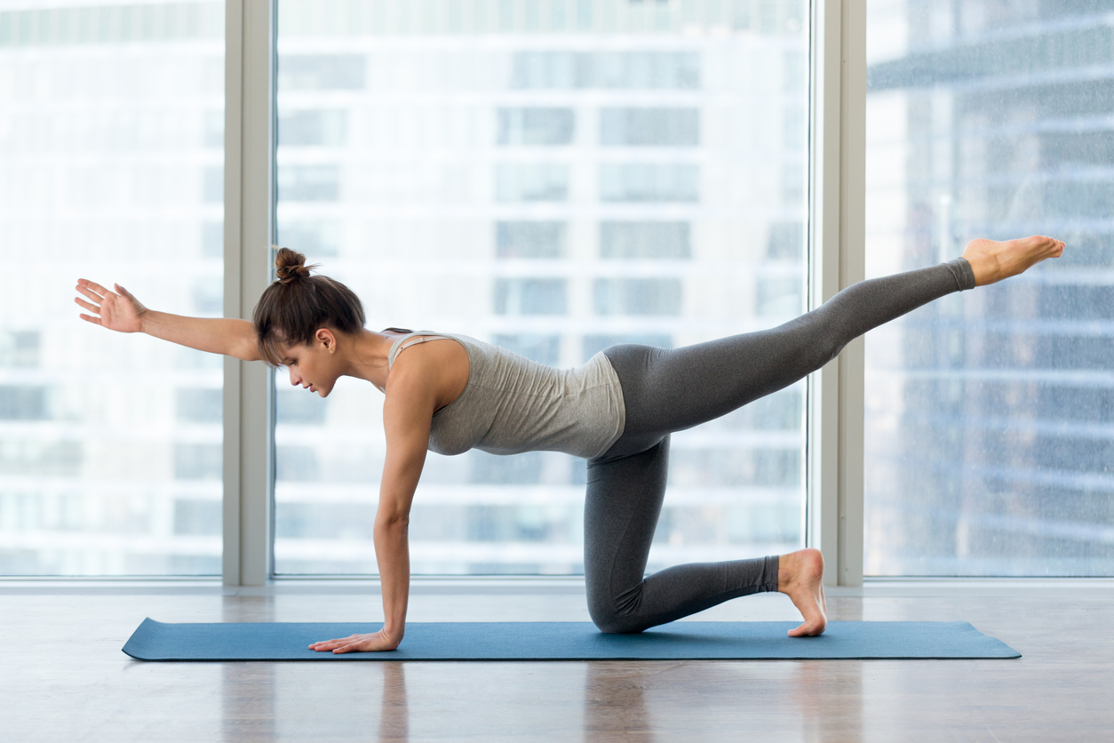 Young sporty woman doing Bird dog yoga pose